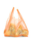 Green apples in plastic bag. Green apples in orange color plastic bag isolated on white background Royalty Free Stock Photography