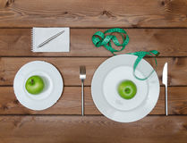 Green apples on plate with knife fork and measure tape Stock Photo