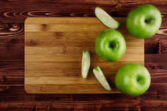 Green apples with slices and bamboo cutting board on brown plank, top view, copy space. Royalty Free Stock Image