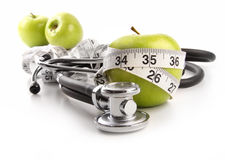 Green apples with stethoscope against white Royalty Free Stock Photos