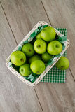 Green apples in white basket. A white wicker basket full of green apples, with emerald green gingham Stock Photography