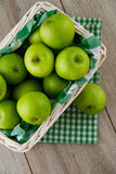 Green apples in white basket. A white wicker basket full of green apples, with emerald green gingham Stock Image
