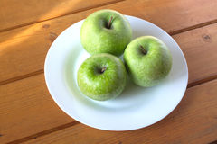 Green apples on white plate on wooden table surface Stock Photos