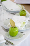 Green apples on white plates. Celebratory laying in white and green color Stock Image