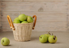 Green apples in a wicker basket on a wooden light background. Stock Photos