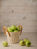 Green apples in a wicker basket on a wooden light background. Stock Photo