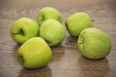 Green apples. On a wooden background Royalty Free Stock Images