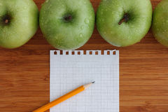 Green apples on a wooden background with sheet of paper and penc Stock Images
