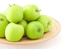 Green apples on wooden plate. Stack of green apples on wooden plate Royalty Free Stock Photography