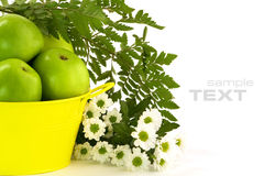 Green apples, yellow bucket and flowers Stock Image