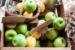 Green apples and yellow lemons in a wood box. Green apples and yellow lemons in a box Royalty Free Stock Photo