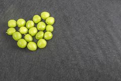 Green apricots in heart form lay on background stock image