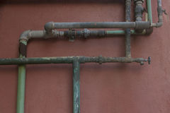 Green and Aqua Rusty Pipes on Coral Stucco Wall Royalty Free Stock Image