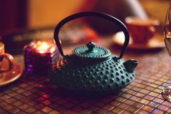 Green Arabic teapot on a mosaic table. Green Arabic teapot on an orange mosaic table in candles light Royalty Free Stock Image