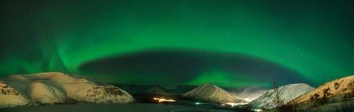 Green arc. Panorama of arc of Aurora polaris above mountains Royalty Free Stock Photo