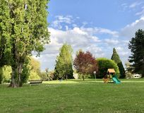 Green area at the residential part of Ferney-Volter, France. Children play ground, bench near the trees, loan stock image