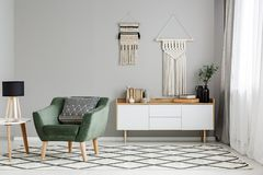 Green armchair on patterned carpet near table with lamp in minim. Al living room interior. Real photo stock image