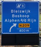 Green arrow above the driving lane indicating that its open on motorway A12 E30 heading Arnhem, utrecht and Zevenhuizen. And junction 8 to N209 local road to stock photos