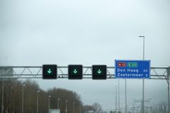 Green arrow above the driving lane indicating that its open on motorway A12 E30 heading Den Haag en Zoetermeer. Green arrow above the driving lane indicating stock images