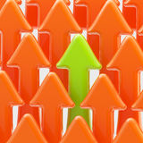 Green arrow among the orange ones Stock Image
