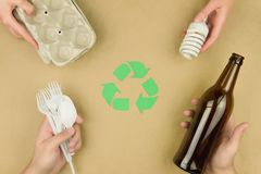 Refuse reuse recycle comcept isolated on brown background. Green arrows recycle symbol and hands with paper egg tray, disposable plastic tableware, glass bottle stock images