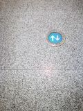 Green arrows sign on granite floor in public transport station or airport passenger terminal. There are copy-space for adding text on the left and below of Royalty Free Stock Photo