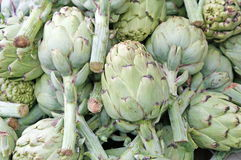 Green artichokes with stems in the grocery store sales Royalty Free Stock Photos