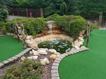 Green artificial grass and rocks on miniature golf course stock photo