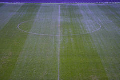 Green artificial grass soccer field with white line and center circle. Stock Photography