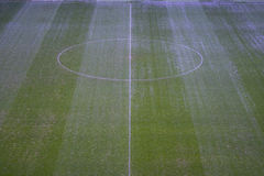 Green artificial grass soccer field with white line and center circle. Stock Photo