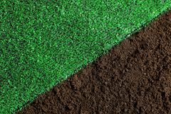 Green artificial grass on soil, top view. Gardening stock image