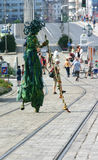 Green artist on stilts walking down the street Royalty Free Stock Image