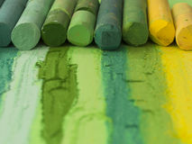 Green artistic crayons in the line. With traces on the paper Stock Photography