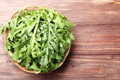 Green arugula leafs. In basket on brown wooden table royalty free stock photo