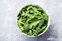 Green arugula leafs. In bowl on grey wooden table royalty free stock photo