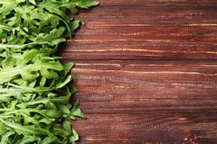 Green arugula leafs. On brown wooden table royalty free stock photography