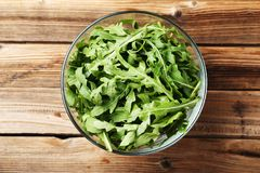 Arugula leafs in glass bowl. Green arugula leafs in glass bowl on brown wooden table royalty free stock image