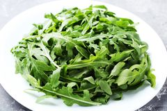 Green arugula leafs. In plate on grey wooden table stock images