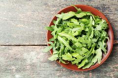 Green arugula leafs. In plate on grey wooden table stock photography