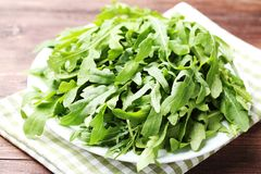 Green arugula leafs. In plate with napkin on wooden table royalty free stock images