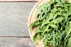 Green arugula leafs. On wooden cutting board royalty free stock image