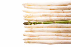 Green Asparagus Amidst Ten White Asparagus Spears Royalty Free Stock Image