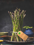 Green asparagus bunch with blank tag standing on dark kitchen table Royalty Free Stock Photography
