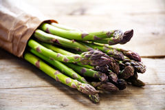 Green asparagus bunch in brown paper on a rustic wooden board, c Stock Image