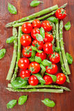 Green asparagus and cherry tomatoes Royalty Free Stock Images