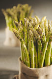 Green asparagus in cloth bags. On canvas background royalty free stock photos