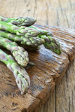 Green asparagus on cutting board. Close up view of fresh green asparagus on a rustic wooden cutting board Royalty Free Stock Photo