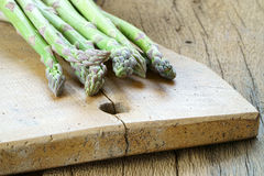 Green asparagus on cutting board. Fresh green asparagus on a rustic wooden cutting board Royalty Free Stock Image