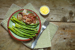 Green asparagus with gammon and dip on an earthenware plate, rus Royalty Free Stock Photography