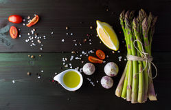 Green asparagus with garlic, salt, lemon, cherry tomato, olive oil and pepper mix on dark background, top view Royalty Free Stock Image